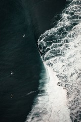 Aerial shot of beautifully breathtaking ocean waves with amazing water textures and surfers around