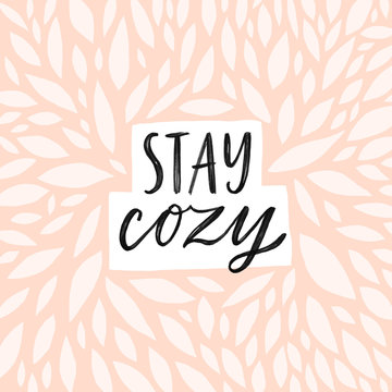 Stay cozy Hand written lettering quote. Cozy phrase for winter or autumn time. Modern calligraphy poster. Minimalist sign. Pastel pink colors and abstract decoration.