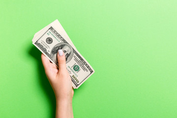 Pack of one hundred dollar bills in femle hands with copy space. Top view of money saving concept on colorful background