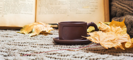 Still life.Brown ceramic cup with tea, dry, yellow autumn leaves. Against the background of an old open book.Hygge concept, autumn mood. free space.Selective focus