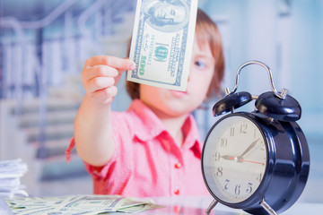 Concept of time and business. Humorous portrait of cute little business child girl holding a sand...