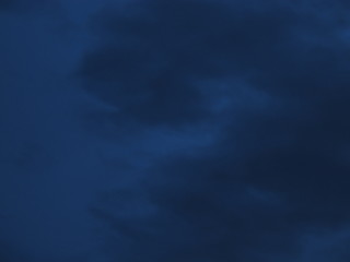 Cloudy nighttime sky in shades of midnight blue to royal blue