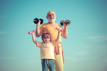 Portrait of senior man and cute child lifting dumbbells. Healthy life and sport concept. Body care and healthcare. Grandfather and child in gym working out with weights.