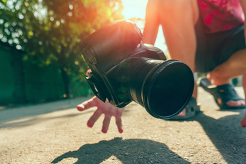 The photographer dropped the camera and catches it with his hands, the camera falls on the asphalt.