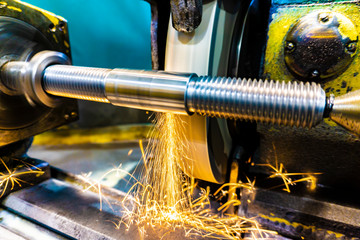 Grinding a threaded shaft on a circular grinding machine with sparks.