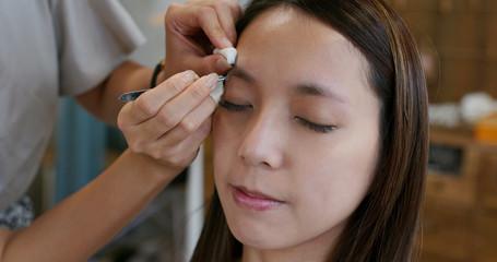 Make up artist shaping eyebrow on female model at studio