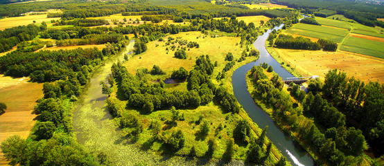Photo Stands Melon A small river in central Poland, flowing among green meadows and forests