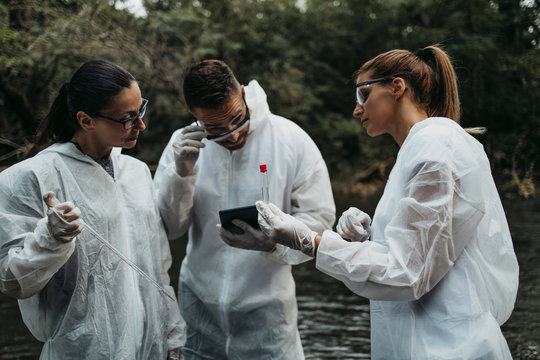 Scientists biologists and researchers in protective suits taking water samples from polluted river.