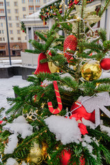 Close up of christmas tree decorated with balls, candy canes and garlands. Festive street arrangement