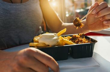 Frau isst Currywurst und Pommes Mayo in Fußgängerzone