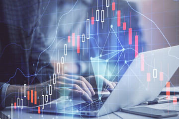 Double exposure of market chart with man working on computer on background. Concept of financial analysis.