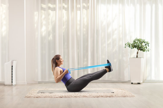 Woman working out at home with an elastic band