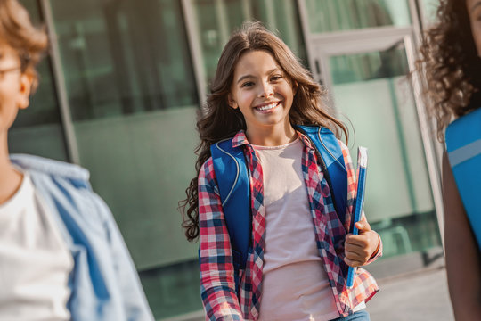 Cheerful preteen caucasian girl with backpack and book going from school and looking at camera