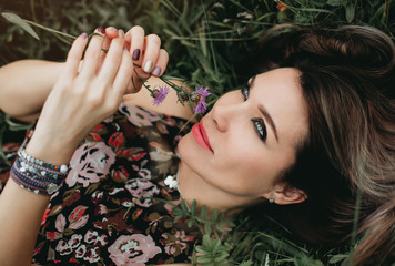 Cadres-photo bureau Portrait of beautiful woman with flower in the grass in the field