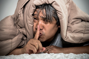 Portrait images of The middle aged man under the blanket, Use the fingers to make a symbol, do not make a noise, to people concept.