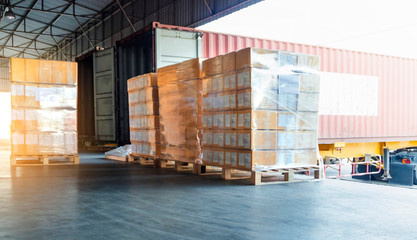 stack of cardboard boxes wrapping plastic on wooden pallet, truck docking load cargo at warehouse, cargo shipment export, freight industry delivery and logistics.