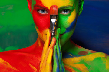 Portrait of the bright beautiful young woman with face art and body art. Contrast colors in creative make-up
