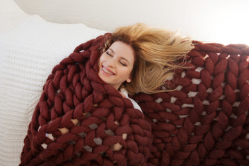 Cute young blonde lying on the bed wrapped in a soft cozy blanket. Warmth and comfort of home