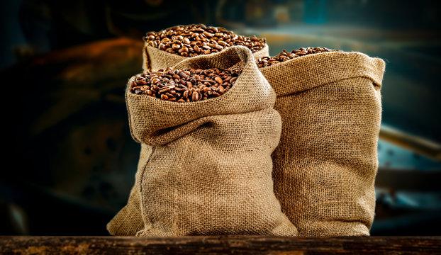 Coffee beans in jute sacks with blurrred coffee machine view