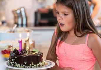 Obraz Urodziny dziecka i impreza z balonami, dmuchanie świec z tortu urodzinowego dla dziecka - fototapety do salonu