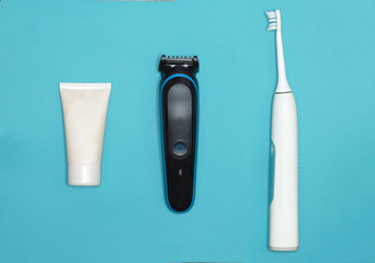 Flat lay composition with men's cosmetic products, personal hygiene items. Travel tourist set on blue background. Top view. Razor, trimmer, after shave cream, electric toothbrush.