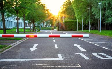 Parkplatzschranke mit Warnleuchte auf Firmengelände abends
