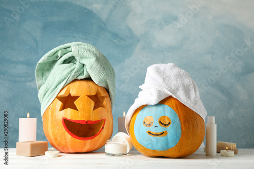 Funny pumpkins and skin care accessories on white background, copy space