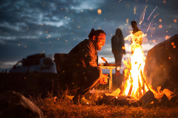 Photo sur Plexiglas Camping Smiling man next to a bonfire in the dark