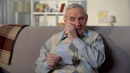 Crying elderly man looking at photo, remembering old lost friend, memories