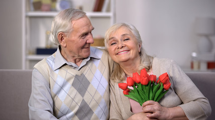 Elderly couple hugging at home, woman holding bunch of tulips, anniversary gift
