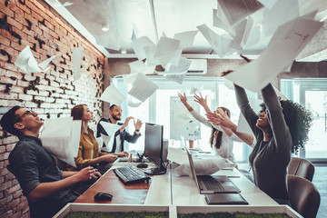 Fototapeta Smiling business people having fun by throwing papers in the air celebrating business success in the modern office. obraz