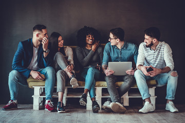 Happy diverse friends group sharing social media app news sitting holding phones, smiling multiracial young people students showing funny videos on laptop
