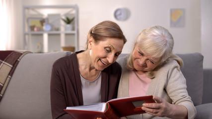 Happy female pensioners admiring old photos in album, retirement leisure, fun