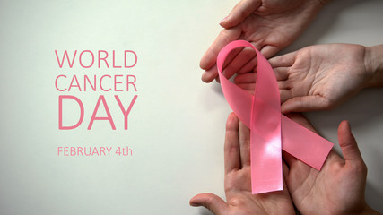 February 4th world cancer day inscription, people hands holding pink ribbon