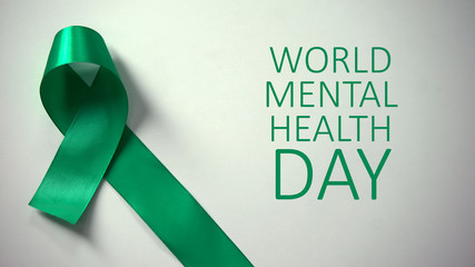 World mental health day inscription, green ribbon on table, awareness campaign