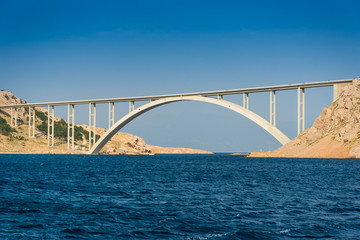 Bridge to the island Krk under blue sky on a sunny summer day. Krk is the big island of the Croatian coast of the Adriatic Sea. Travel landscape
