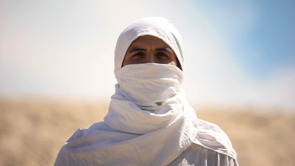 Bedouin in white clothes looking at camera, islamic religion and traditions