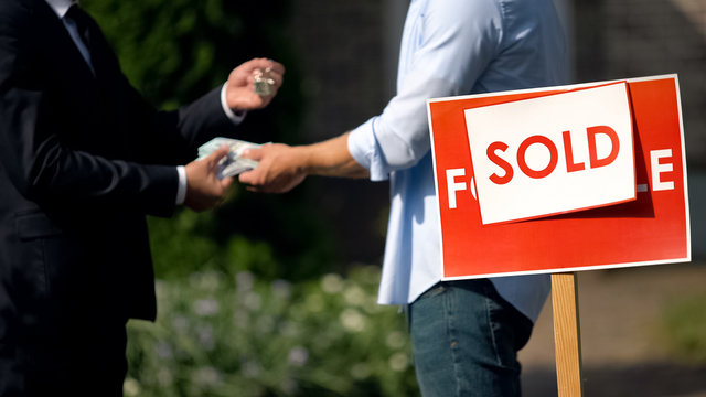 Estate agent and man exchanging money and house keys against sold signboard