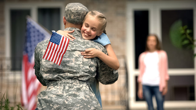 Cheerful daughter hugging father soldier, long awaited meeting, homecome