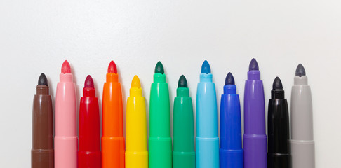 Multi-colored felt-tip pens, markers on white.