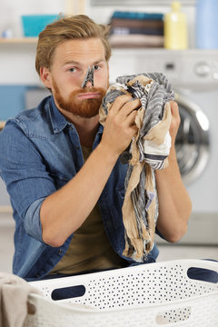 young man holding smelly and dirty laundry