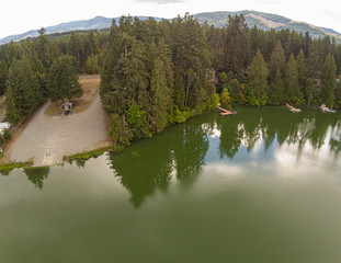 Stunning aerial photography of Thurston County's Clear Lake with the trees and clouds and the surrounding mountains reflecting in the waters in summer time. Located in Yelm, Washington.