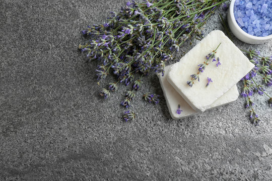 Hand made soap bars with lavender flowers on grey stone table, flat lay. Space for text