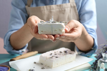 Wall Mural - Woman holding hand made soap bar with lavender flowers at light blue wooden table, closeup