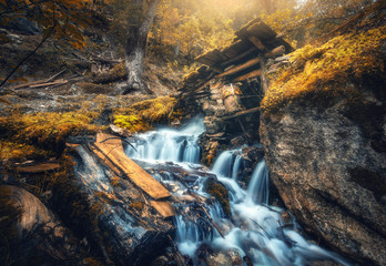 Wall Mural - Stony well in colorful forest with little waterfall in mountain river at sunset in autumn. Landscape with stones in water, building, orange trees, waterfall and vibrant foliage in fall. Nature