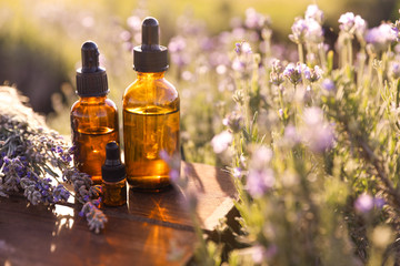 Bottles of lavender essential oil on wooden table in field. Space for text