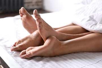 Passionate young couple having sex on bed at home, closeup of legs
