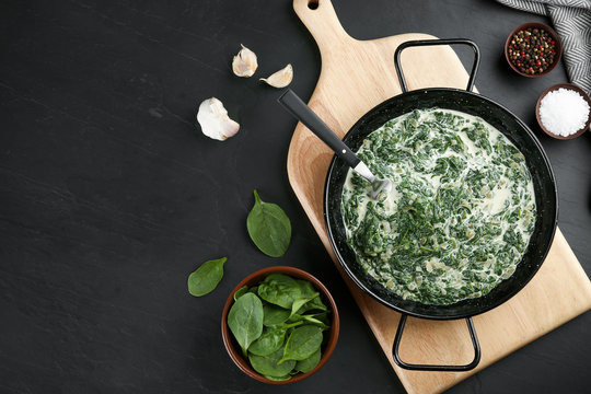 Tasty spinach dip in frying pan on black table, flat lay. Space for text