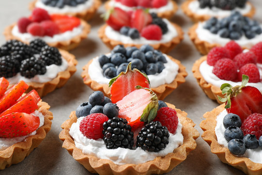 Many different berry tarts on table. Delicious pastries