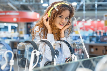 Foto auf Acrylglas Musikladen Red-haired girl standing at the counter in the store of electronic equipment choosing new headphones to buy. Listening to music in big headphones. Sales season at the Mall